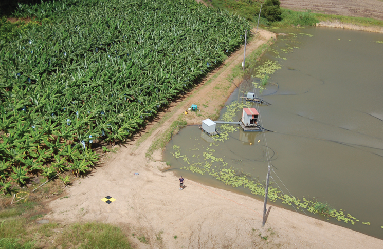 Banana crop monitoring showing the UAV operator (centre), landing target and obstacles–wires, water. Photo: Joe Urli