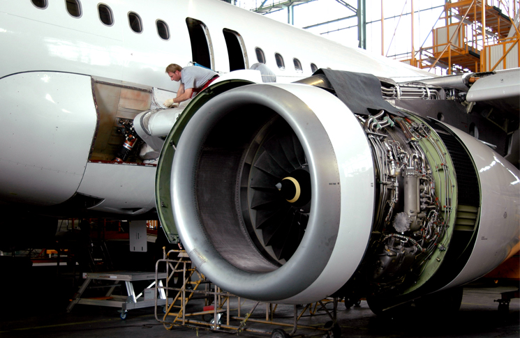Maintenance crew working on engine in hangar