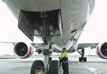 Inspector examining nosewheel of jet aircraft