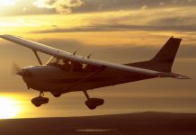 Cessna 172R flying at sunset.