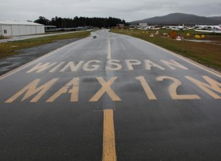 A wet taxiway labeled with the words Wingspan Max 12M at Canberra Airport in August 2020. Taxiway and unserviceability cones appear on the grass next to the taxiway.