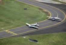 Aerial view of a Piper and Cessna lined up on the taxiway at Cairns Airport.