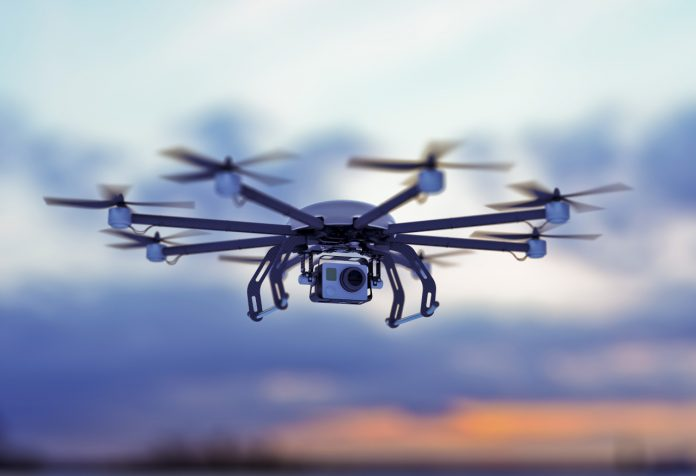 Octocopter drone flying against a dusk sky.