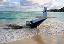 The wreckage of a light aircraft on a beach.