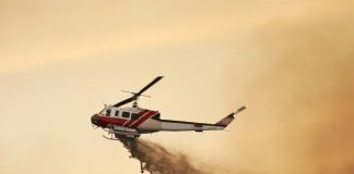 Fire fighting helicopter dropping water against a smoky orange sky.
