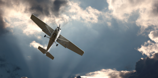 Image of a small plane flying out of dark clouds with some sunlight